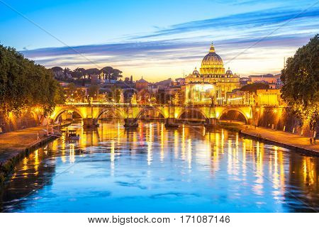 Cityscape of Rome at twilight with San Pietro cathedral, Sant'Angelo bridge and Tevere river illuminated by city lights of Roma in Italy