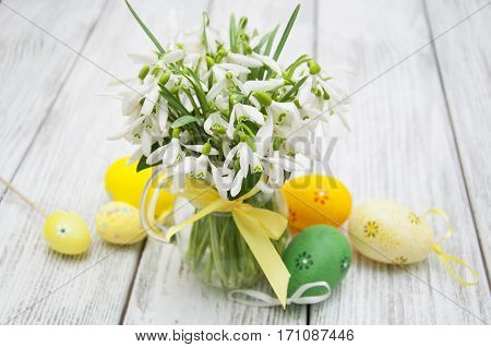 Beautiful snowdrops in a vase with Easter eggs on a wooden background