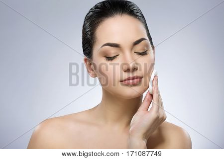 Brunette girl with black fixed hair behind, closed eyes and naked shoulders, cleaning face with cotton pad at gray studio background, copy space, portrait.