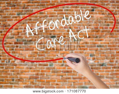 Woman Hand Writing Affordable Care Act With Black Marker On Visual Screen