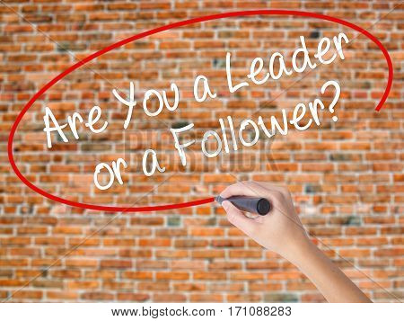 Woman Hand Writing Are You A Leader Or A Follower? With Black Marker On Visual Screen