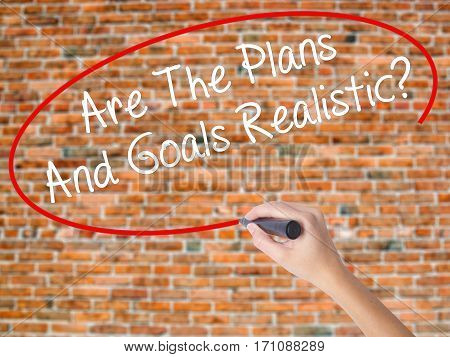Woman Hand Writing Are The Plans And Goals Realistic? With Black Marker On Visual Screen.