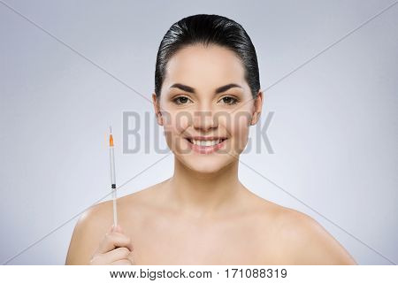 Nice girl with black fixed hair behind, dark big eyes and naked shoulders looking at camera and smiling, holding syringe, portrait, copy space.