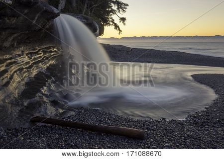 Waterfall pouring into the Pacific Ocean at sunrise Vancouver Island Canada