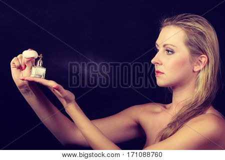 Smell elegance concept. Beautiful elegant blonde woman with necklace applying perfume after shower on naked body studio shot on dark background