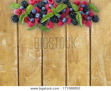 Various fresh summer berries on wooden background. Ripe blueberries raspberries and blackberries. Berries at border of image with copy space for text.