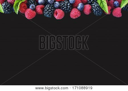 Various fresh summer berries isolated on black background. Ripe blueberries raspberries and blackberries with basil leaves. Berries at border of image with copy space for text. Top view.