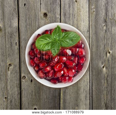 Pomegranate seeds on wooden background. Red grains of a pomegranate in ceramic bowl. Sweet and juicy garnet with copy space for text. Top view.