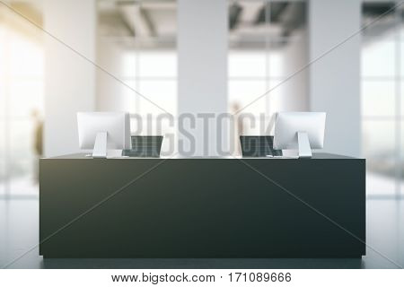 Front view of black reception desk with computers in blurry concrete interior with daylight. Business concept. 3D Rendering