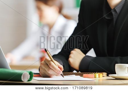 Close up of male hands doing paperwork at modern workplace with coffee cup stickers and other items