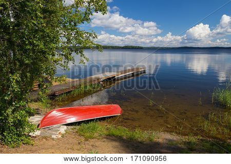 red boat on a lakes coast and sky with clouds