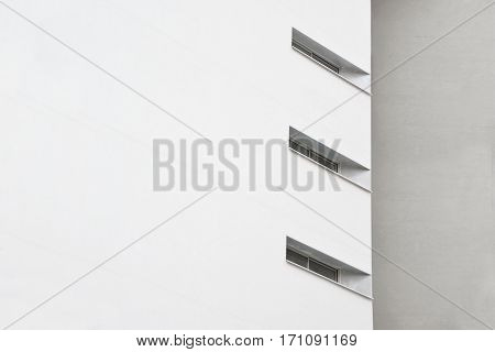 Abstract architecture background. White facade and diagonal windows next to a grey brick wall.