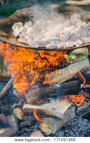 Outdoor frying pork meat on a wood fire with flames