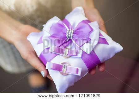 the golden rings on a pillow with a purple bow