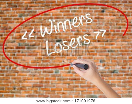 Woman Hand Writing Winners - Losers  With Black Marker On Visual Screen