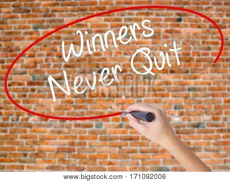 Woman Hand Writing Winners Never Quit With Black Marker On Visual Screen