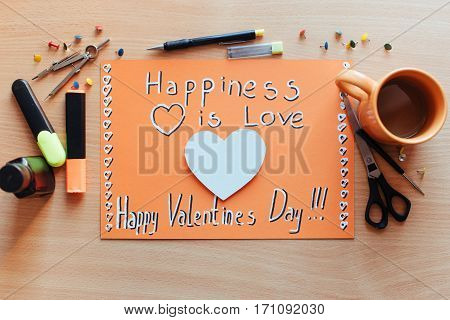 Orange sheet painted with a red heart with lots of stationary objects. Valentine's Day.