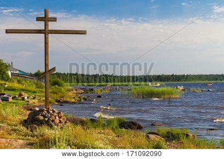 Orthodox Christianity cross on the shore of northen lake
