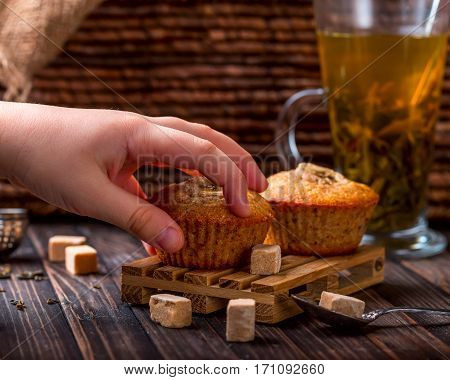 Children's hand takes the banana cake. Wooden background. Sugar and cup with green tea near. Selective focus