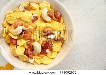 Tasty cornflakes with nuts and raisins on table