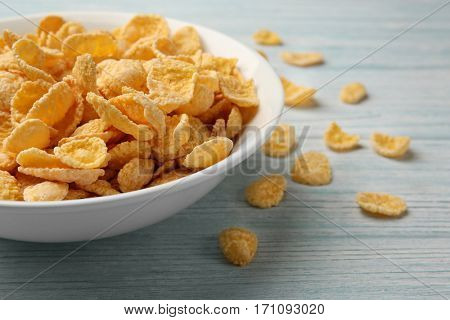 Bowl with cornflakes on white wooden background, closeup