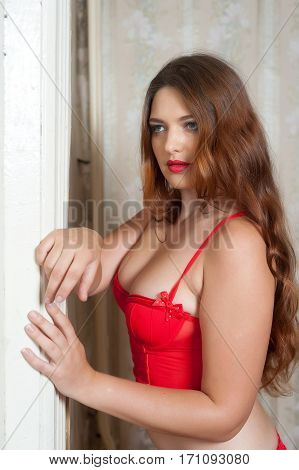 Pretty woman in red corset with red coat inside old room