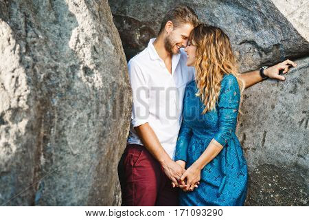 Nice couple standing together very close to each other between rocks, outdoor. Beloved holding hands of each other. Man looking at girl and she has closed eyes. Profile. Girl wearing blue dress and man wearing white shirt and claret trousers, he has styli