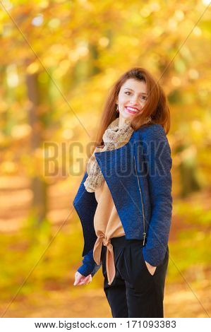 Modest girl in autumnal enviroment. Young fashionable woman walking in park. Fashion nature relax recreation concept.