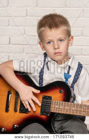 Little beautiful boy playing on electric guitar sitting on a chair near brick wall
