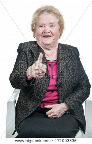Smiling old woman sitting on a chair shows the thumb up, isolated on a white background