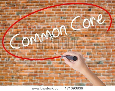 Woman Hand Writing Common Core With Black Marker On Visual Screen