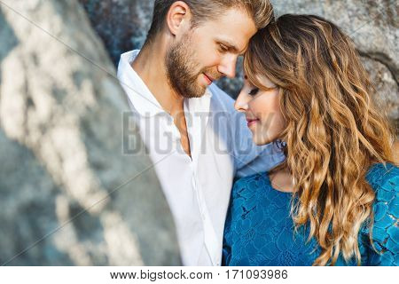 Cute couple standing together very close to each other between rocks, outdoor. Beloved holding hands of each other. Man looking at girl and she has closed eyes. Profile, head and shoulders, closeup. Girl wearing blue dress and man wearing white shirt, he