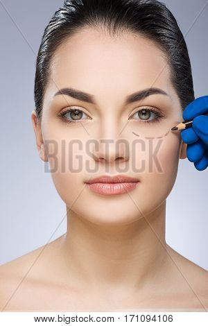 Plastic surgeon drawing dashed line under eye of girl. Beautiful girl. Hand in blue glove holding pencil. Plastic surgery, beauty portrait
