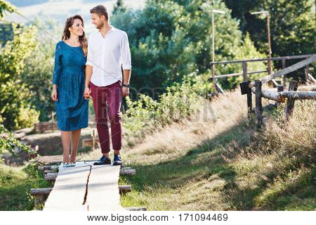 Joyful couple standing together, outdoor, countryside. Beloved looking at each other, holding hands of each other and smiling. Girl wearing blue dress and light blue shoes and man wearing white shirt and claret trousers. Full body
