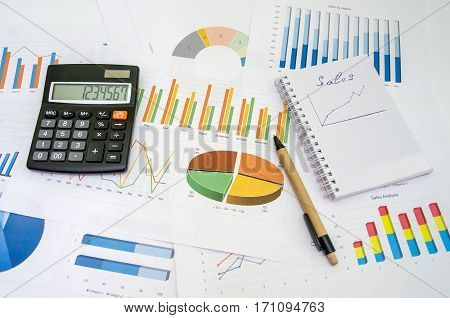 Financial accounting graphs analysis with pen and calculator