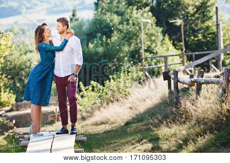 Nice couple standing together, outdoor, countryside. Beloved looking at each other and smiling. Girl embracing her boyfriend. Woman wearing blue dress and light blue shoes and man wearing white shirt, claret trousers and black shoes. Full body