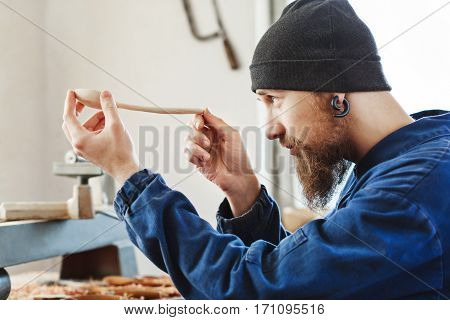 Man with a beard wearing blue jeans suit and black hat holding and looking at wooden spoon, woodcarving, portrait, copy space.
