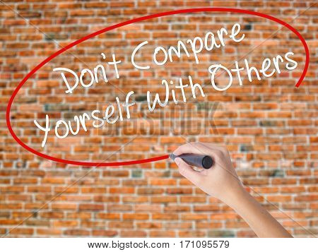 Woman Hand Writing Don't Compare Yourself With Others With Black Marker On Visual Screen