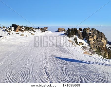 Panorama of winter mountains over the clouds, ski slopes in bulgarian alpine ski resort Borovets