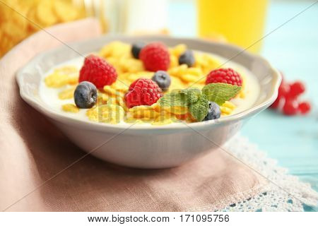 Tasty cornflakes with raspberries and blueberries, close up