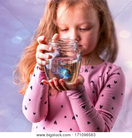 Baby girl in pink dress holding a aquarium with blue fish. The concept of care for Pets. Gift. Selective focus