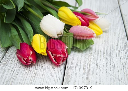 Bouquet of colorful tulips on a wooden board