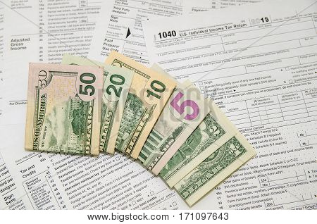 individual tax forms with dollar bills close up