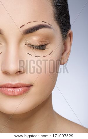 Dashed lines around eyes of girl. Beautiful girl with closed eyes. Plastic surgery, beauty portrait, half face, closeup
