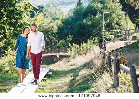 Nice couple walking together, outdoor, in the countryside. Beloved holding hands of each other and smiling. Girl looking down and man looking straight. Woman wearing blue dress and light blue shoes and man wearing white shirt, claret trousers and black sh