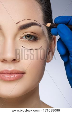 Plastic surgeon drawing dashed line around eye of girl. Hand in blue glove holding pencil. Plastic surgery, beauty portrait, half face, closeup