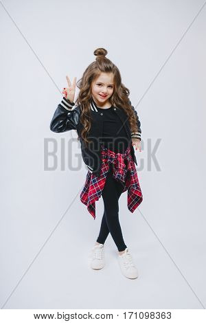 Portrait of little hipster girl in bomber jacket. Posing. Curly modern hairstyle. Showing peace by fingers. Smiling. Studio