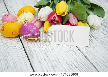 Colorful tulip bouquet blank greeting card with Easter eggs on a white wooden background