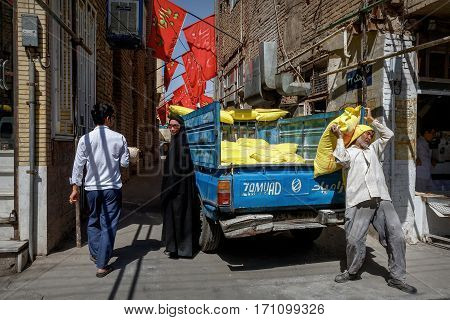 Iran Persia Kashan - September 2016: Local man unloads a truck in the street. Hard physical labor.