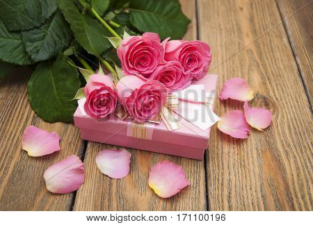 Beautiful pink roses with gift box on a wooden background